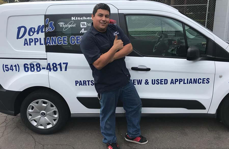 A Don's Appliance employee in front of one of their fleet vehicles